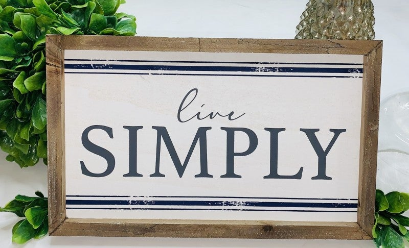 "Wooden framed ""live simply"" sign"